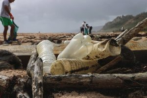 Shallow focus, plastic bottles on a beach. Dark clouds loom as passersby walk among the plastic and debris