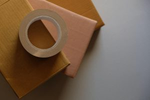 Packaging materials flat-lay. A roll of brown tape is placed on some boxes, stacked and arranged in a fan shape.