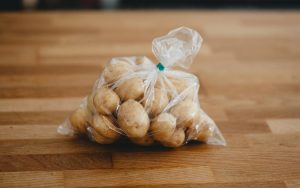 New potatoes in a clear polythene bag, with a green tape seal at the top, placed on a butcher's block.