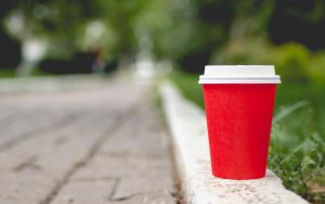 A red disposable coffee cup with white plastic lid on, placed on the kerb in a park.